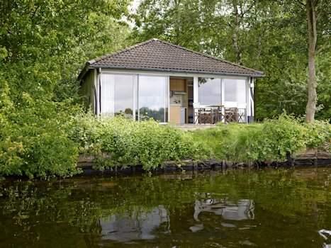 Huisje in bos aan het water
